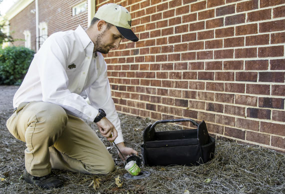 termite technician changing out station